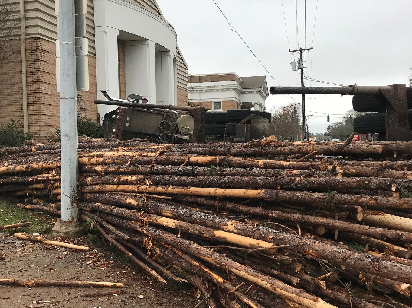 Log truck overturns on N. Pine Street