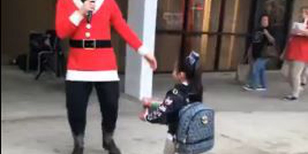 Elementary school teacher sings Christmas carols to students